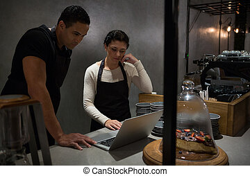 Waiter and waitresses using laptop at counter
