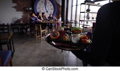 Crop shot of server bringing food for group of people sitting in restaurant.