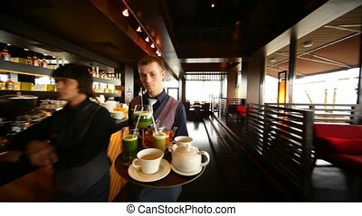 Waiter carries tray with drinks in restaurant lounge, flying motion