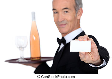 waiter carrying bottle of wine with glass and showing his personal card