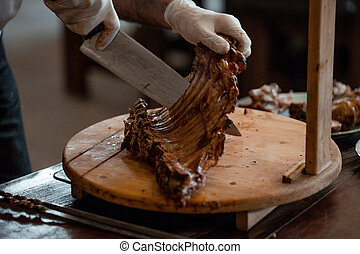Waiter chops grilled lamb ribs on wooden board with big knife