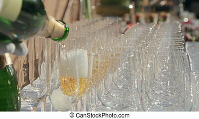 Waiter fills empty glasses with champagne at a banquet -...