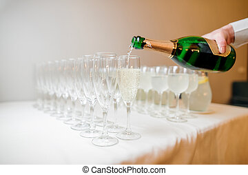 Waiter hand pouring champagne into glasses