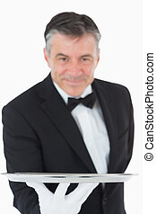 Waiter holding a silver tray out