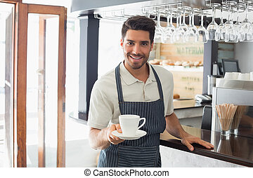 Waiter holding cup of coffee at café - Young ...