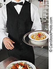 Waiter Holding Dish In Kitchen