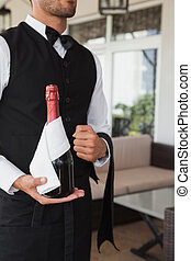 Waiter holding magnum of champagne in the patio of...