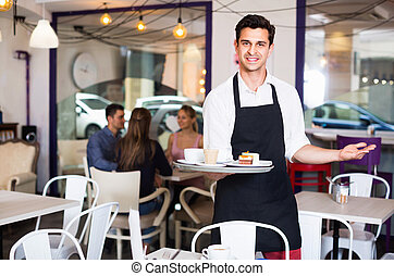 Cheerful positive waiter holding served tray meeting visitors at pastry bar