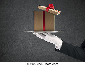 Waiter holds a Christmas present in a tray
