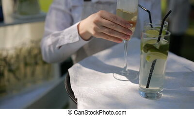 Waiter in a white shirt carries lemonade and champagne
