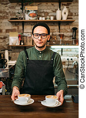 Waiter in black apron holds two cups of coffee