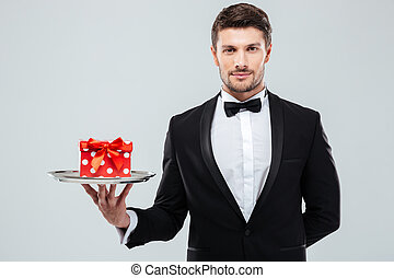Waiter in tuxedo with bowtie holding present box on tray