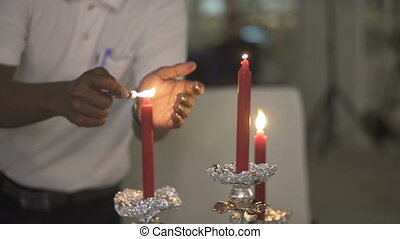 Waiter lights the candles in the restaurant
