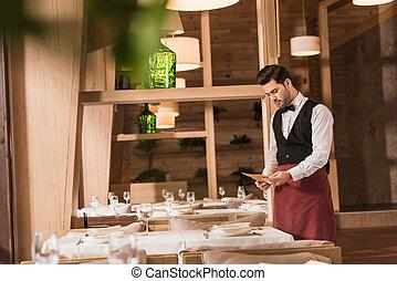 Waiter looking at menu