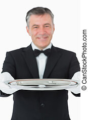 Waiter looking at the camera while holding a silver tray