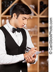 Waiter making notes. Confident young sommelier writing something at his note pad while standing in front of shelf with wine bottles