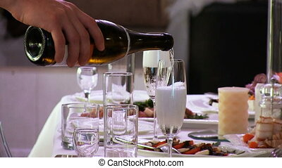 Waiter man pours the champagne white sparkling wine into the...