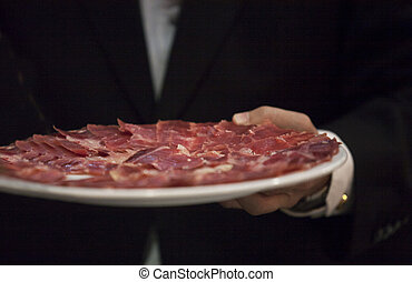 Waiter offering slices of Iberian cured ham on plate
