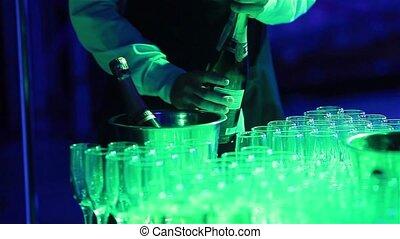 Waiter opening bottle of champagne