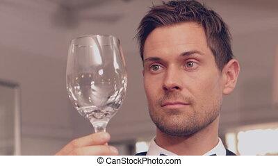 Waiter polishing wine glass in slow motion