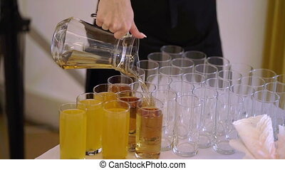 Waiter pouring juice to glasses