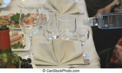 Waiter pouring the stemware of vodka indoors - Waiter...