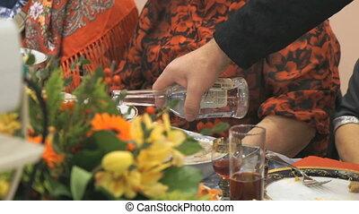 Waiter pouring the stemware of vodka indoors - Waiter...