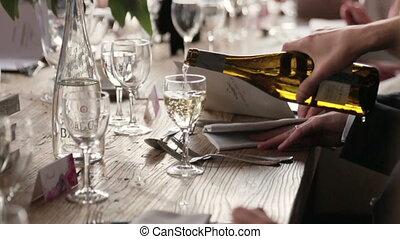 Waiter pours foaming champagne close up. Wedding celebration in Paris