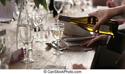 Waiter pours foaming champagne close up. Wedding celebration in Paris