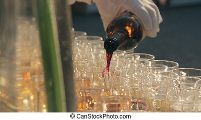 Waiter pours red wine into glasses on catering - Waiter...