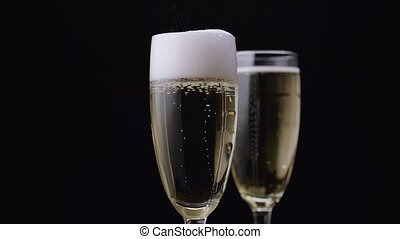 Waiter pours the champagne into the glass. Black background....
