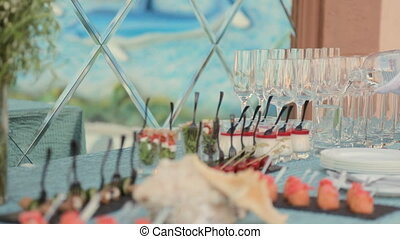 Waiter pours the water into glasses on a table with snacks on banquet