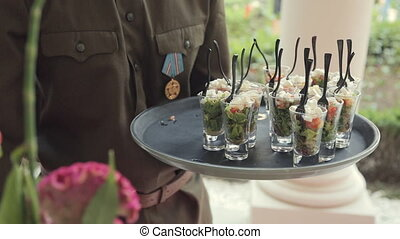 Waiter puts on the table salad in individual containers at a banquet in honor of the victory