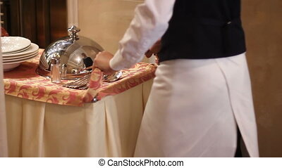 waiter rolls into the room table with a hot dish under the cloche and plates with appliances