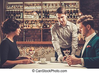 Waiter serving a desert to guests at restaurant.