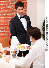 Waiter serving a meal in a restaurant