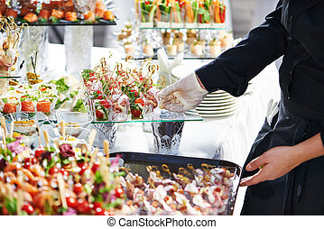 Waiter serving catering table