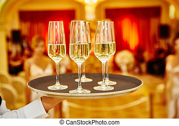 Waiter serving champagne on a tray. Full glasses of...