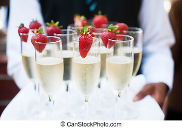 Waiter serving champagne on a tray with strawberries