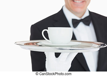 Waiter serving coffee on silver tray