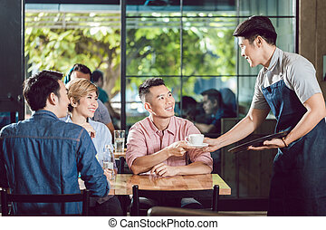 Waiter serving coffee to the customer