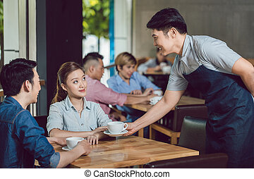 Waiter serving coffee to young woman in the cafe