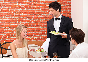 Waiter serving couple in restaurant