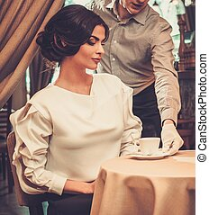 Waiter serving cup of coffee to beautiful woman guest in a restaurant.