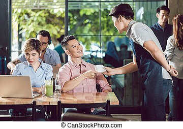Waiter serving cup of coffee to the customer