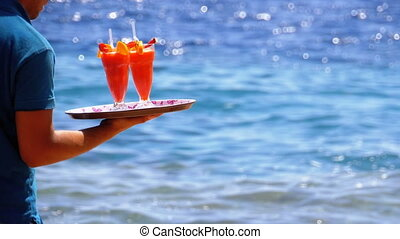 Waiter Serving Drinks on the Beach, Egypt. Waiter holding a tray with tropical juices