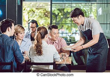 Waiter serving food in the restaurant