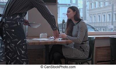waiter serving restaurant guest at table - waiter delivers...