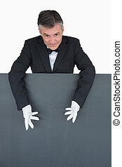 Smiling waiter showng the blank grey board