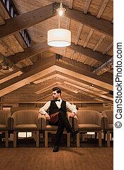 Waiter sitting in armchair